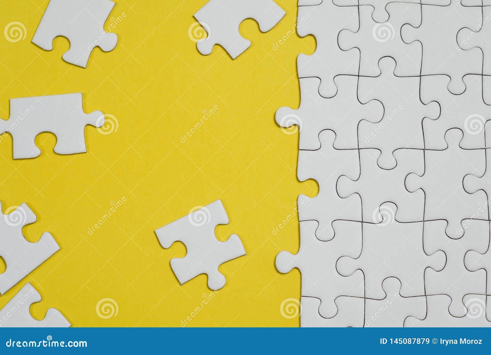 Frammento di un puzzle bianco piegato e un mucchio degli elementi spettinati di puzzle contro lo sfondo di una superficie gialla