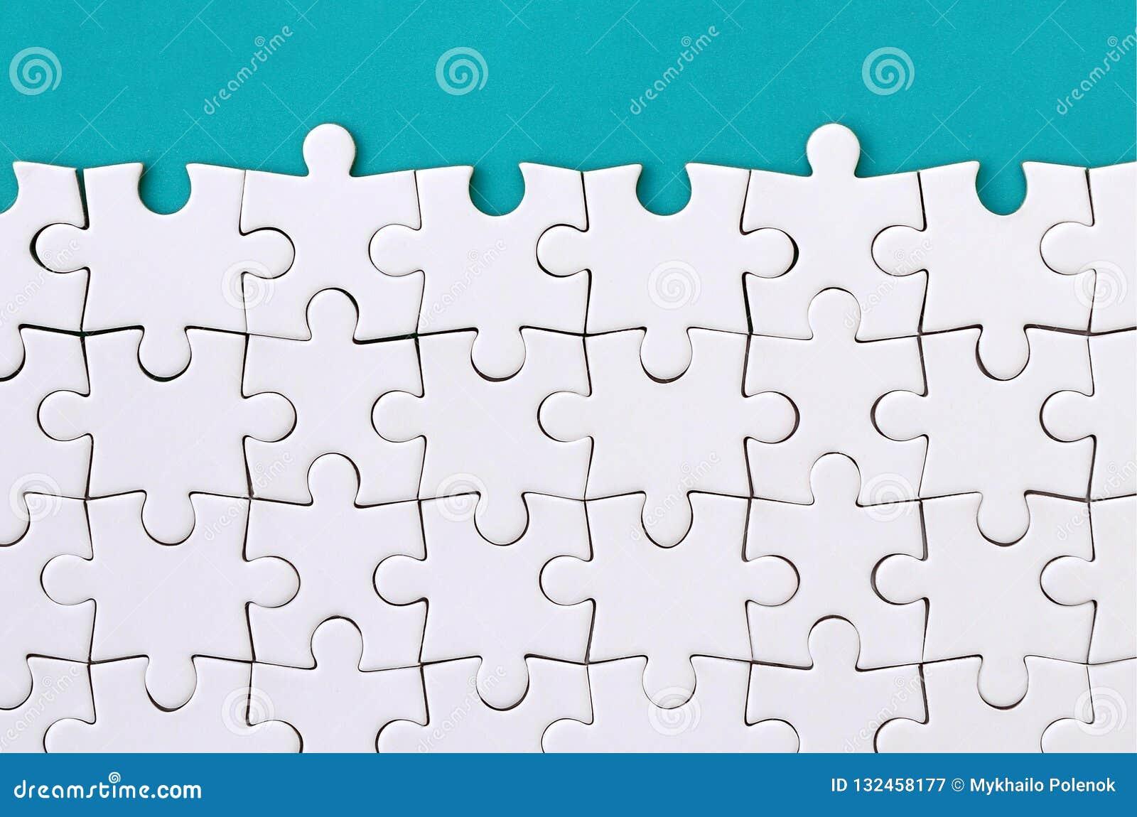 Frammento di un puzzle bianco piegato sui precedenti di una superficie blu della plastica Foto di struttura con lo spazio della c