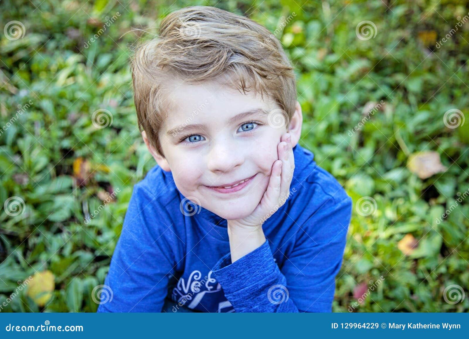 Framsida av att le den lyckliga pojken utanför