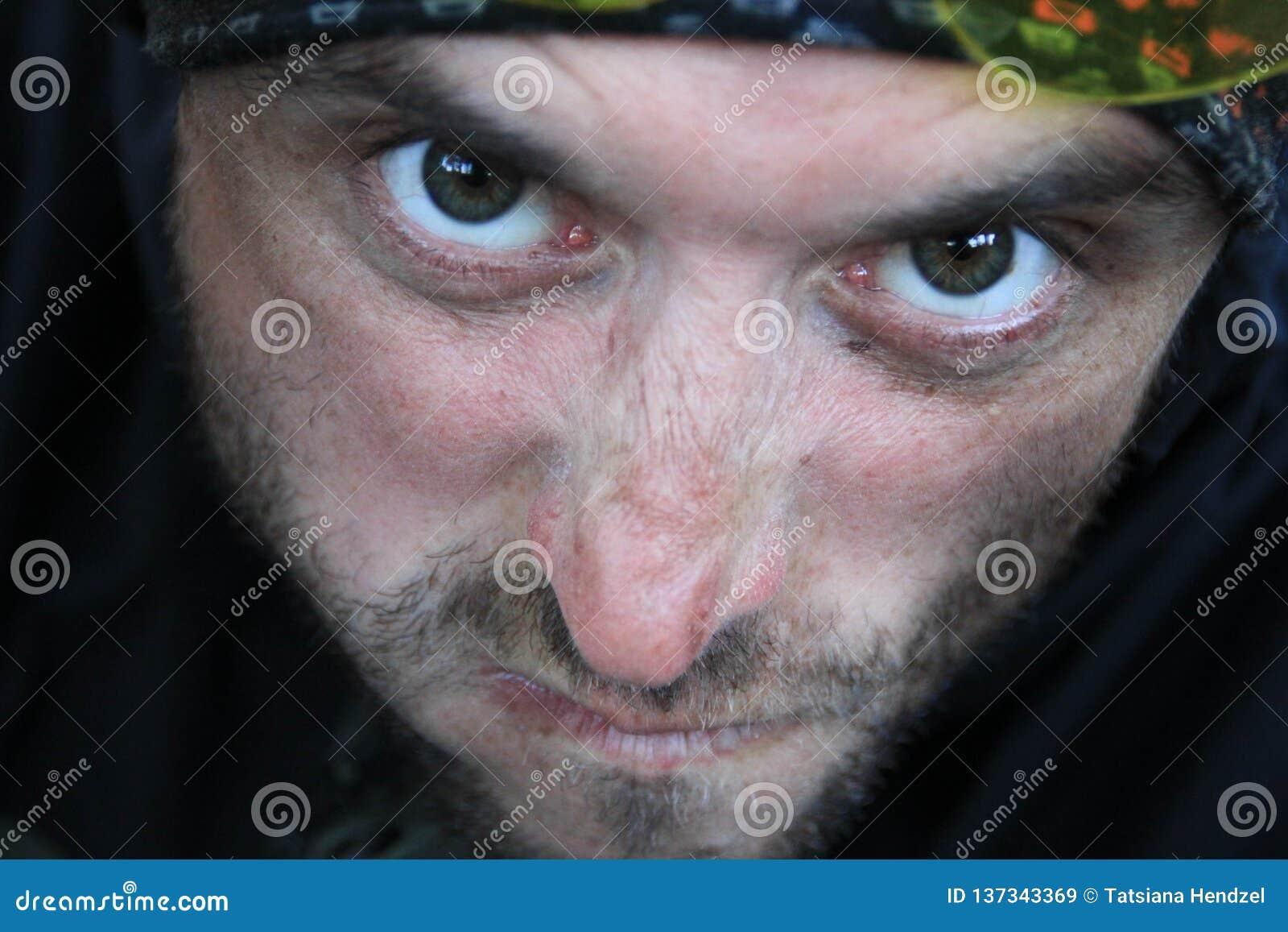 Framsidan av en vit ung man förvrids av ilska och agression Han har en ondskefull besatt blick från under hans panna