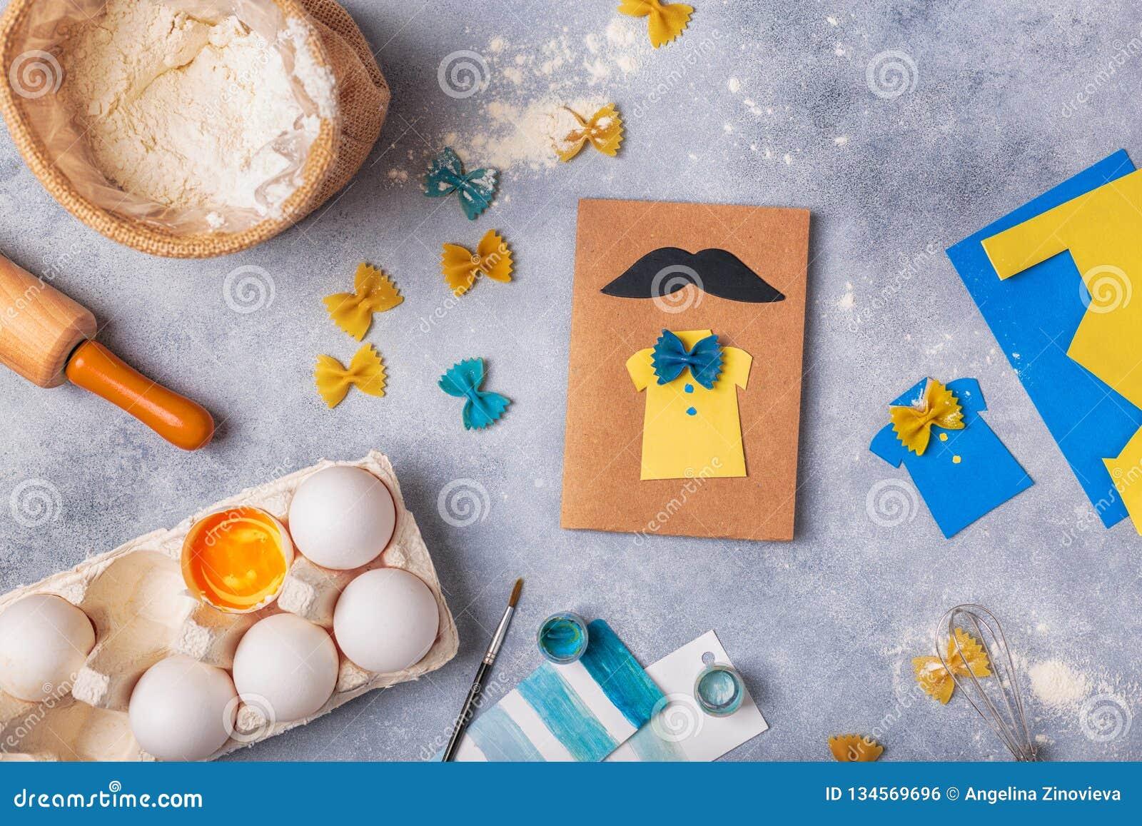 Framställning av hälsningkortet för faderdag Skjorta med fjärilen från pasta Kort från papper moustache Barns konstprojekt