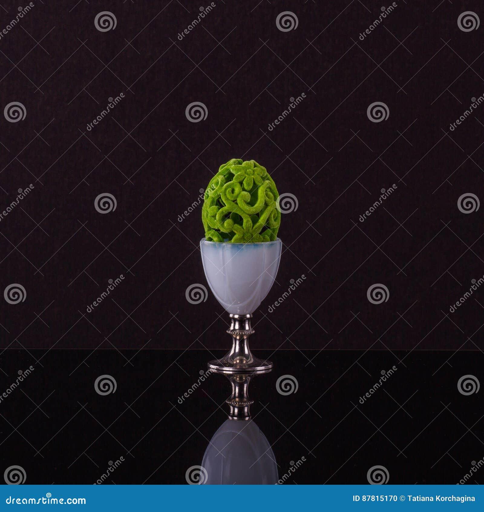 Framstående äggkopp med det flotta gröna påskägget för elegante