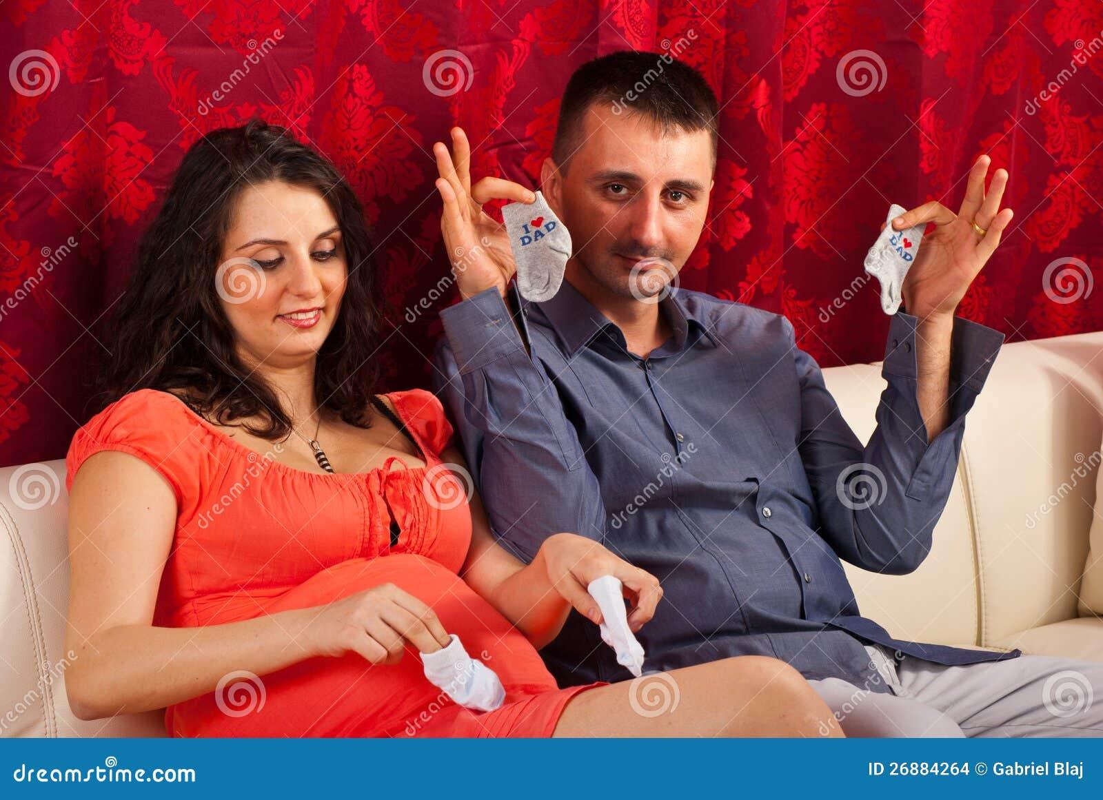 Framtida föräldrar som visar babystorkdukar