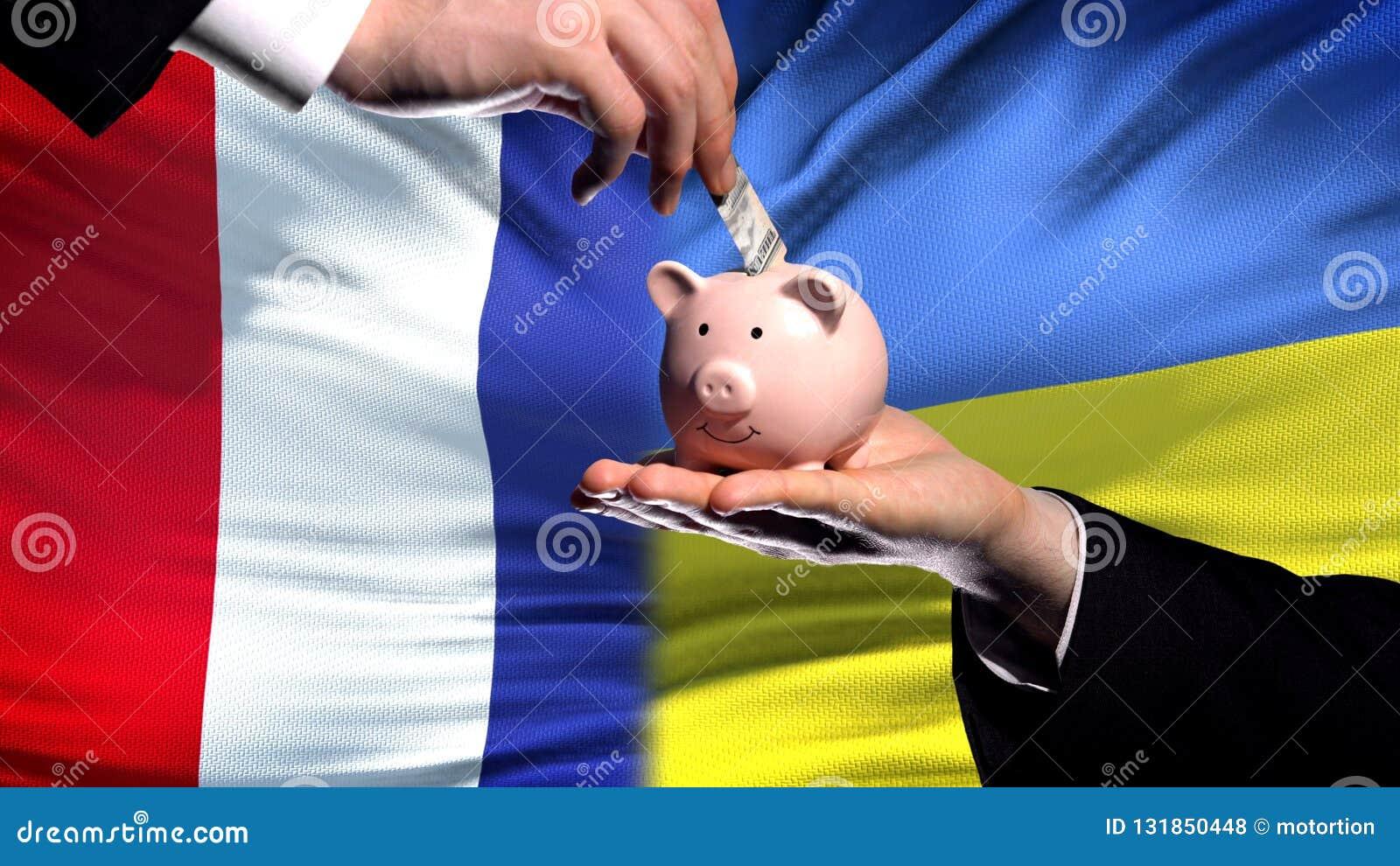 Francja inwestycja w Ukraina, ręki kładzenia pieniądze w piggybank na chorągwianym tle