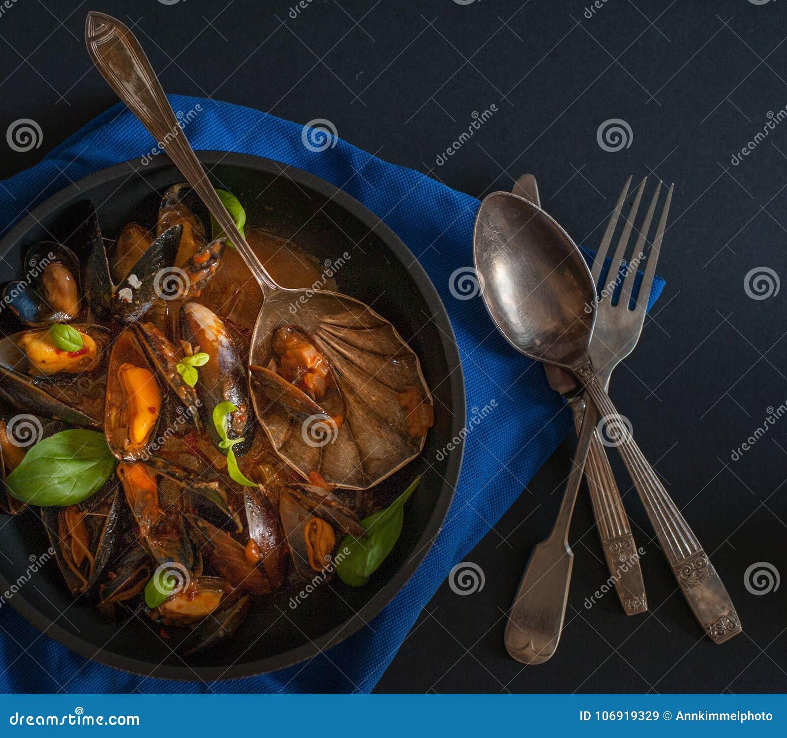 Francuska kuchnia: odparowani mięśnie z świeżym basilem opuszczają w czarnym garnku wpólnie