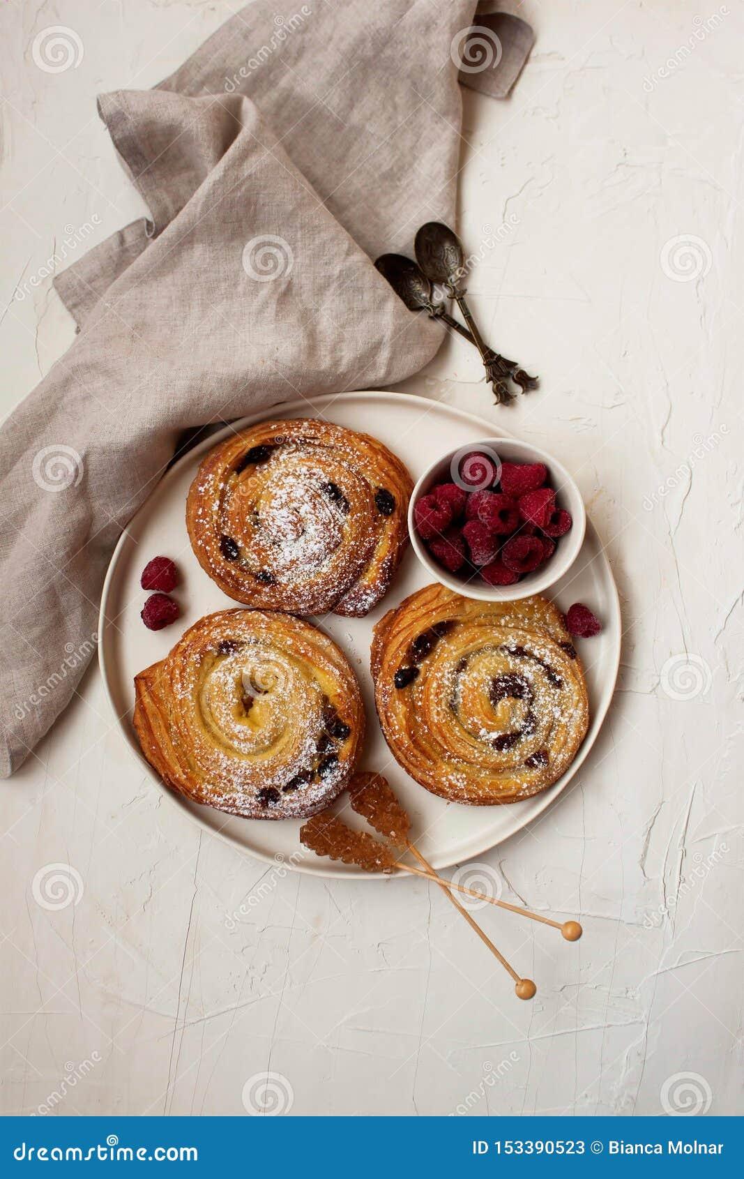 Francuski śniadanie z cynamonowymi rolkami i malinkami