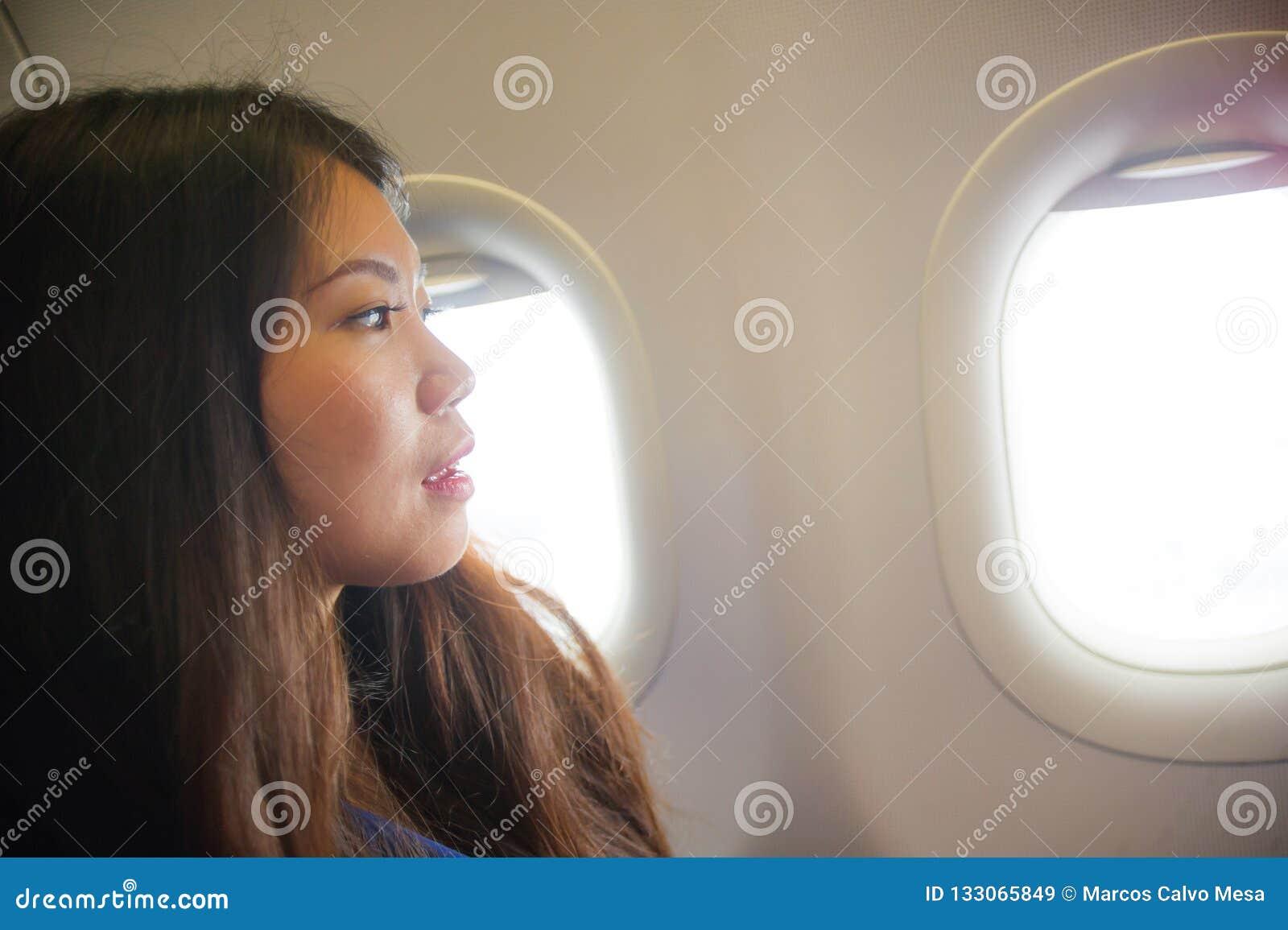 Frank stående för livsstil av den unga lyckliga och härliga asiatiska koreanska kvinnan som reser för ferier inom flygplankabinen
