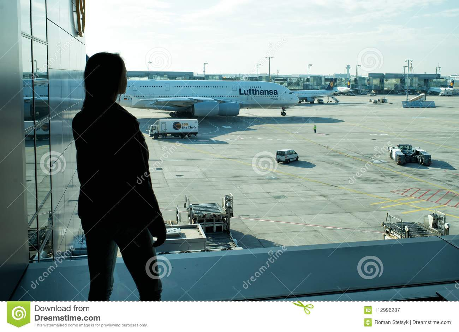 Frankfurt-am-Main, Duitsland - Oktober 11, 2015: het meisjessilhouet bekijkt vliegtuigen op vliegveldgrond op zonnige dag Vrouw i