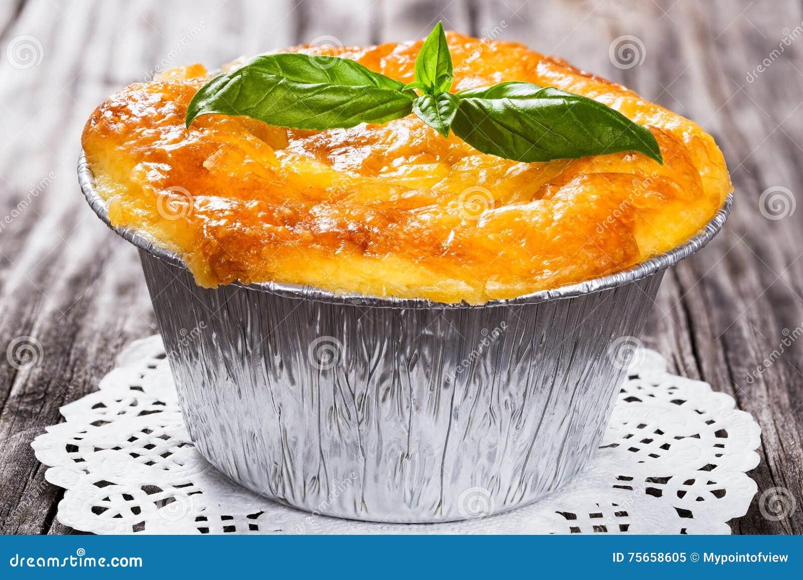 Franse cuisine- julienne Paddestoel, kippen en kaasgratin in de vorm van Aluminiumfoliemini baking met basilicumbladeren wordt ve