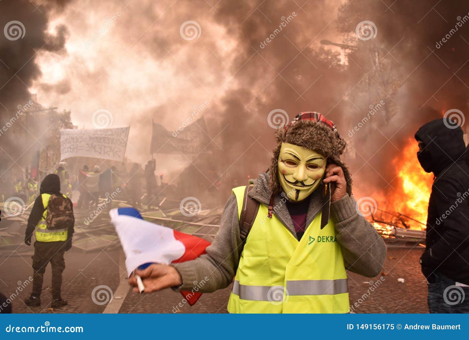 Fransk gul västprotesterare som bär den Guy Fawkes maskeringen på en demonstration i Paris