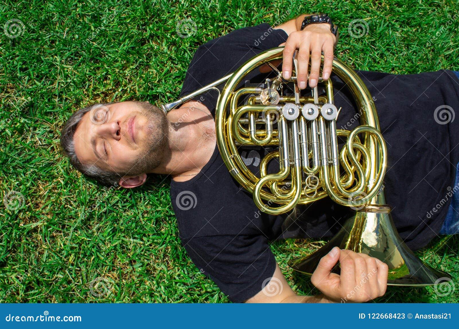 Fransk horn En man i en T-tröja ligger på gräset och rymmer ett musikinstrument Waldhorn