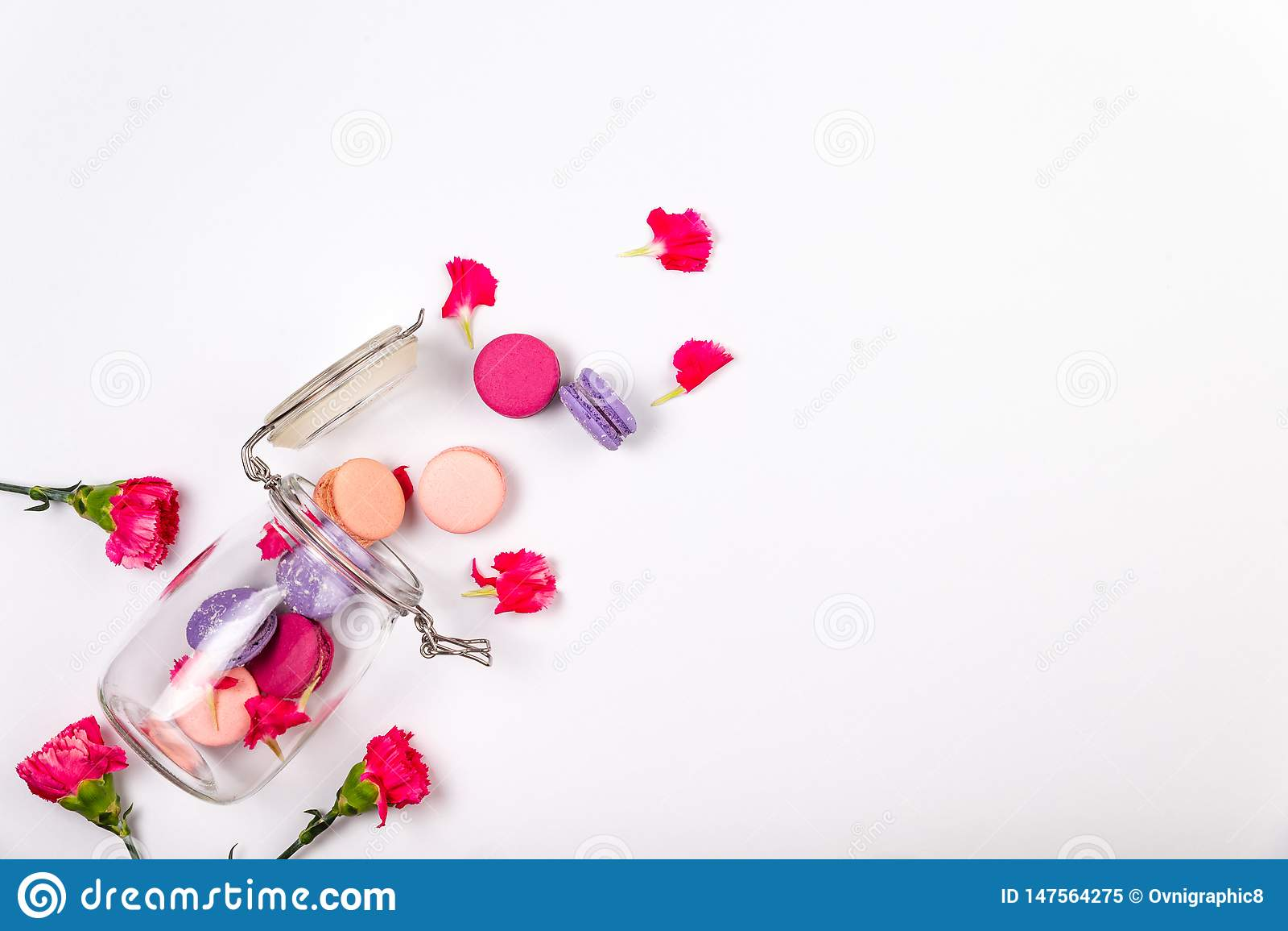 Franska rosa och purpurfärgade macarons eller makron, rosa inkarnationkronblad och blommor som faller ut ur en exponeringsglaskru