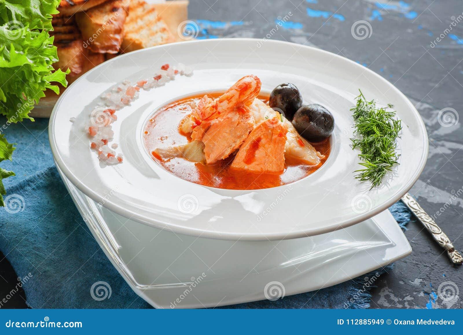 Franskan fiskar soppabouillabaissen med skaldjur, laxfilén, räka, rich anstrykning, läcker matställe i en härlig vit