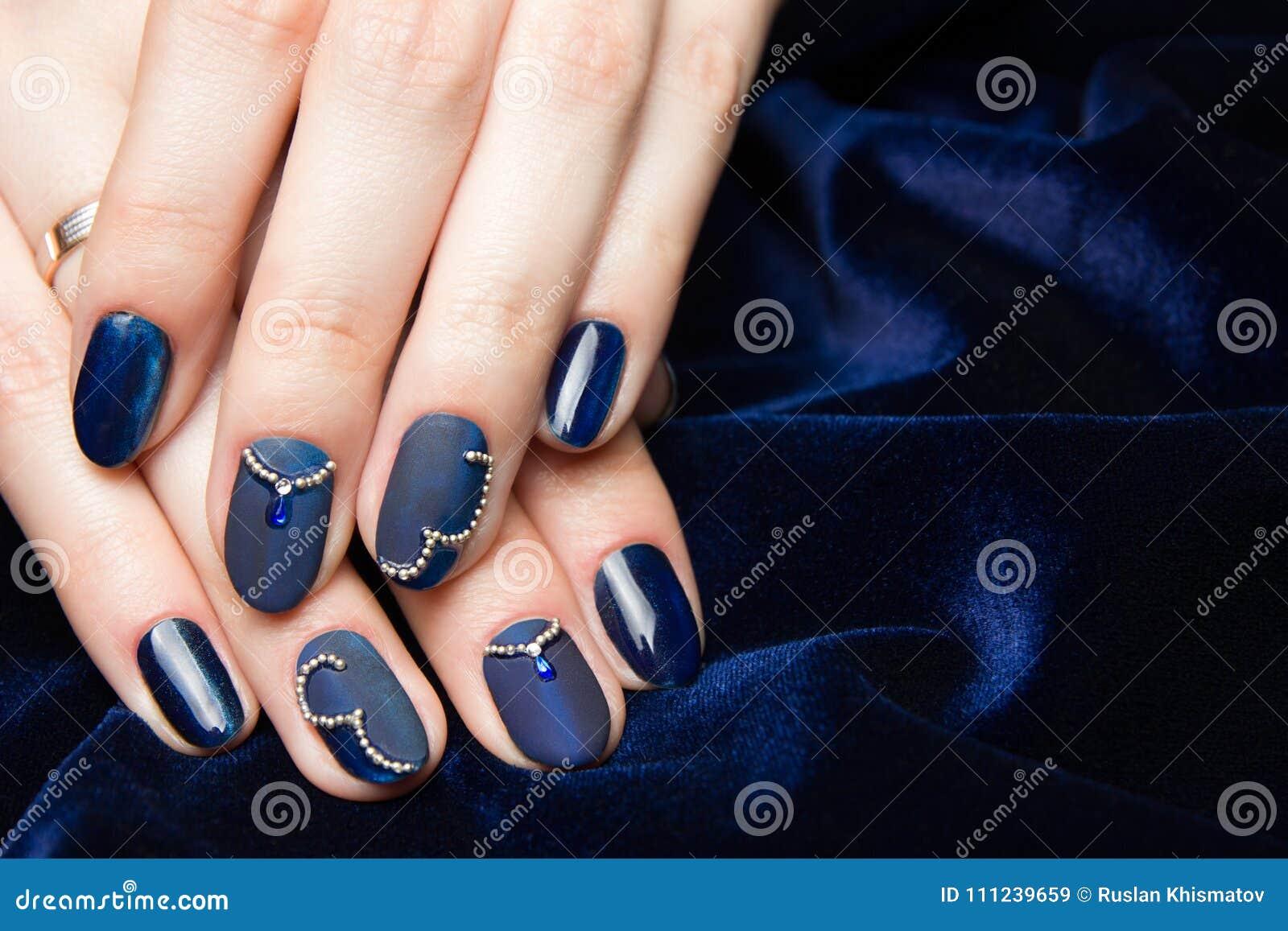 Französische Maniküre - schöne manikürte weibliche Hände mit blauer Maniküre mit Bergkristallen auf dunkelblauem Hintergrund