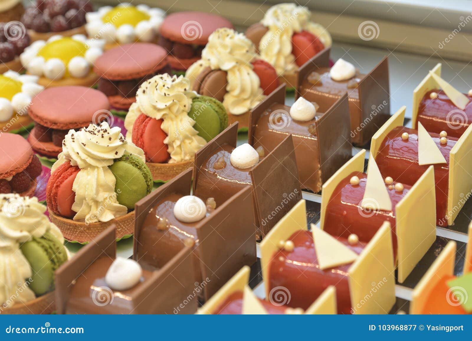 Französisches Gebäck Schokoladenkuchenmacaron und -andere zeigen an einen Süßigkeitenshop an