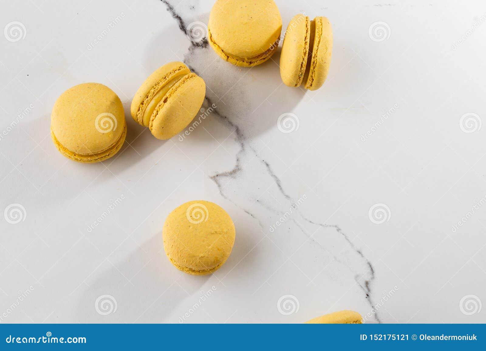 Franz?sische Makronen Selektiver Fokus Schöne gelbe Makronen auf Marmorhintergrund Stilvoller Anordnungsbonbon