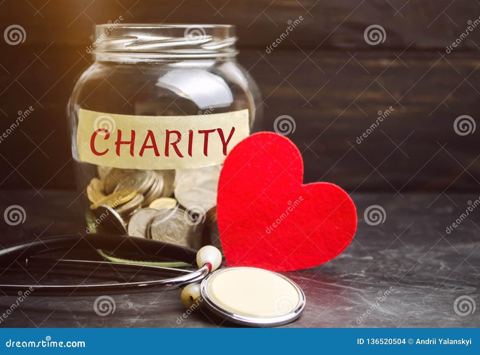 Frasco de vidro com a caridade das palavras e o coração O conceito de acumular o dinheiro para doações saving Ajuda médica social