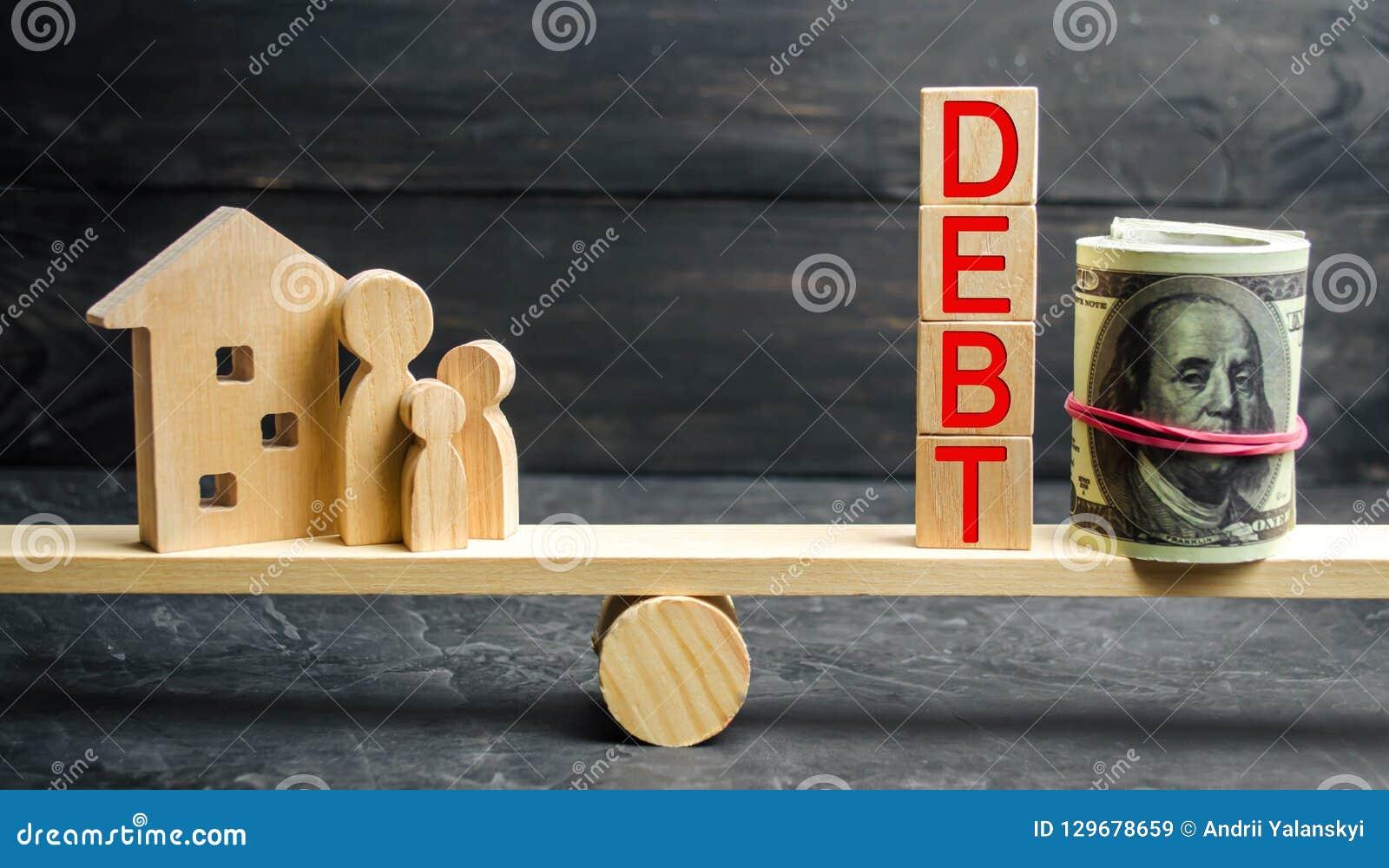 Frasco de vidro com moedas e a inscrição 'débito ', família e casa de madeira Bens imobiliários, economias de casa, conceito do m