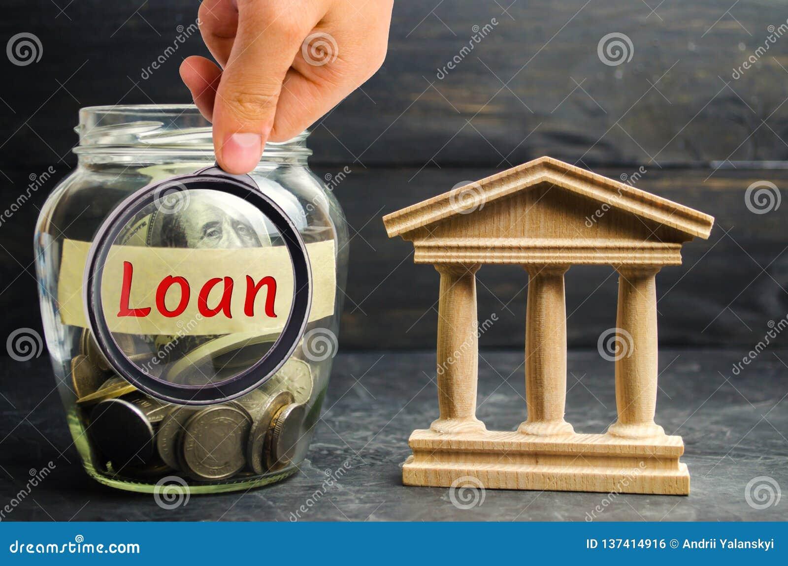 Frasco de vidro com moedas e o empréstimo da palavra e uma construção do estado Peça o dinheiro, tome um empréstimo ou um crédito