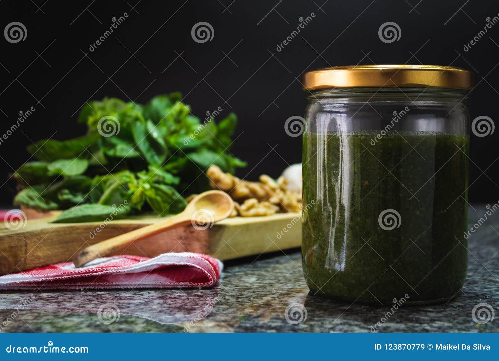 Frasco do molho do Pesto com ingredientes