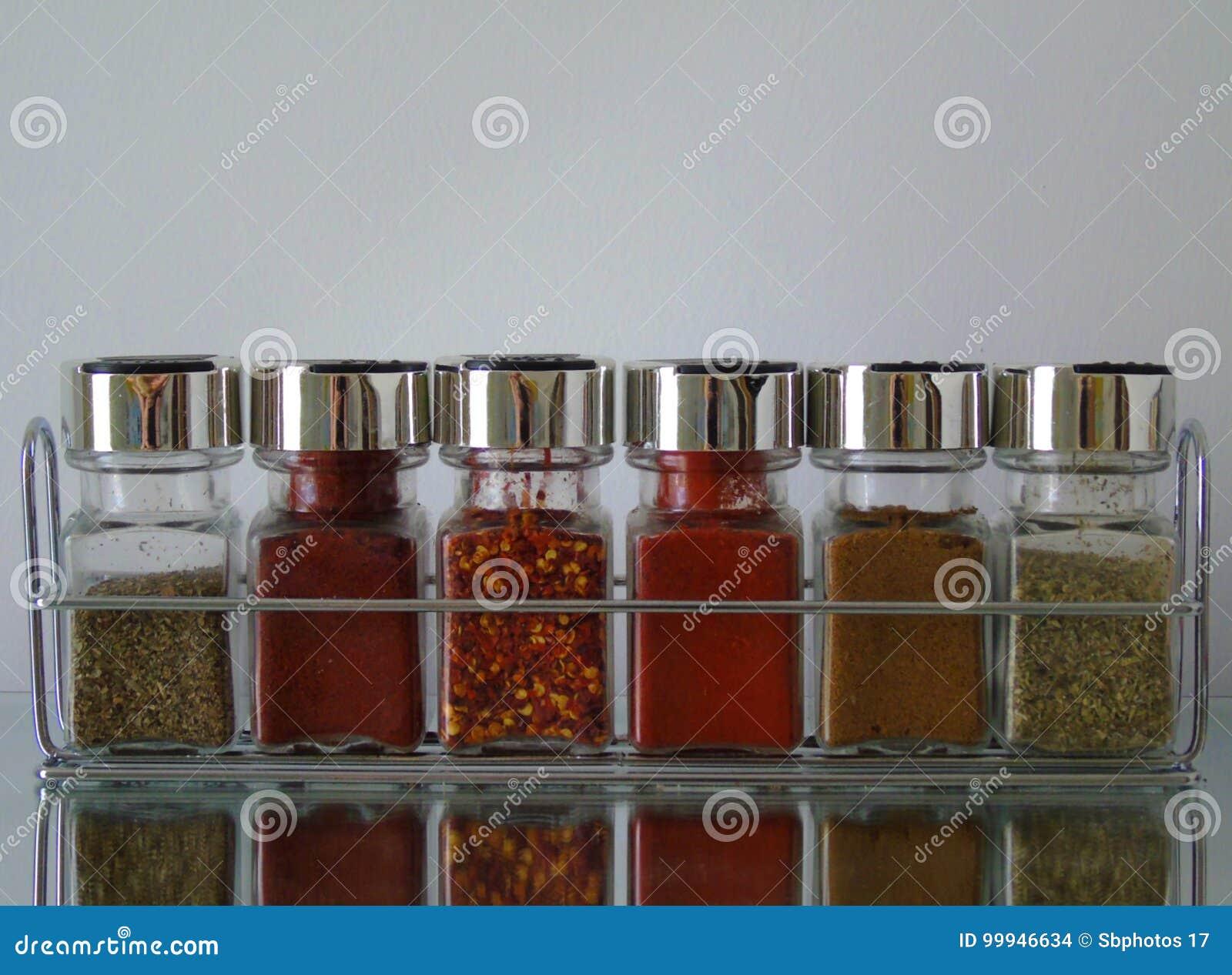 Frascos das ervas e das especiarias na cremalheira de especiaria