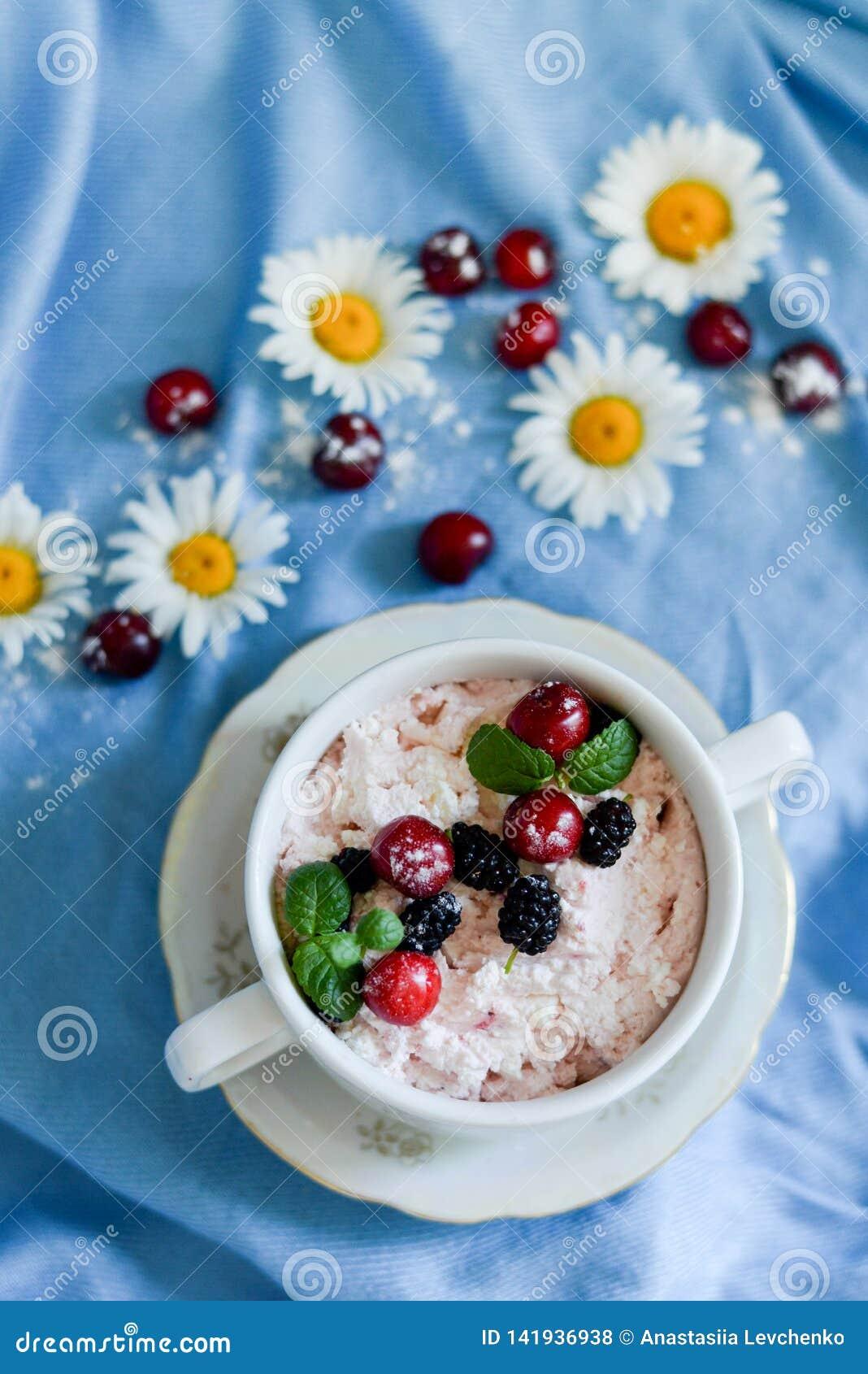 Frascos do iogurte branco natural com salada de fruto com fruto, as bagas e a hortel? cor-de-rosa do drag?o na tabela Comer saud?