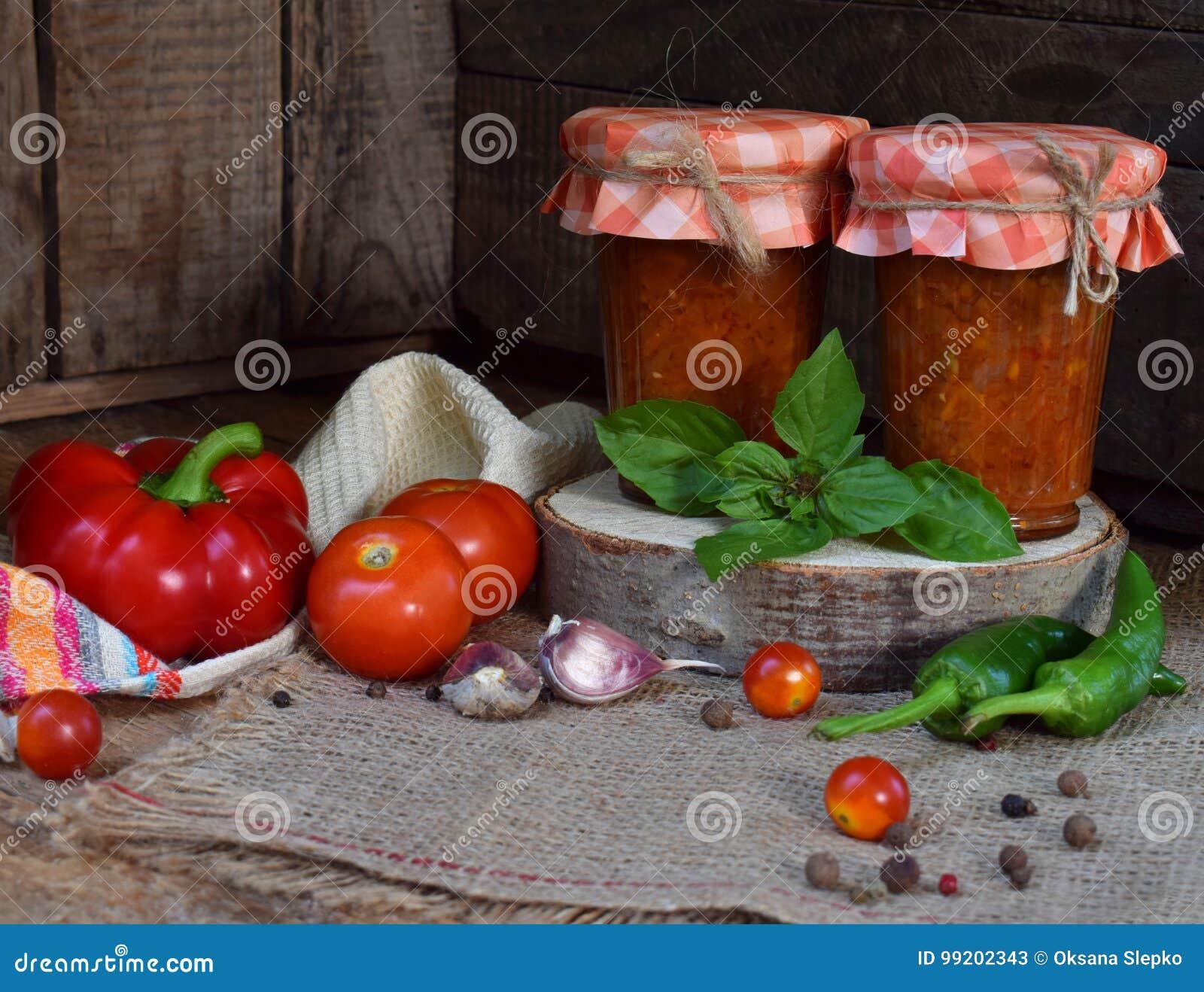 Frascos do molho de tomate com pimentão, pimenta e alho Molho, lecho ou adjika bolonhês preservação enlatar