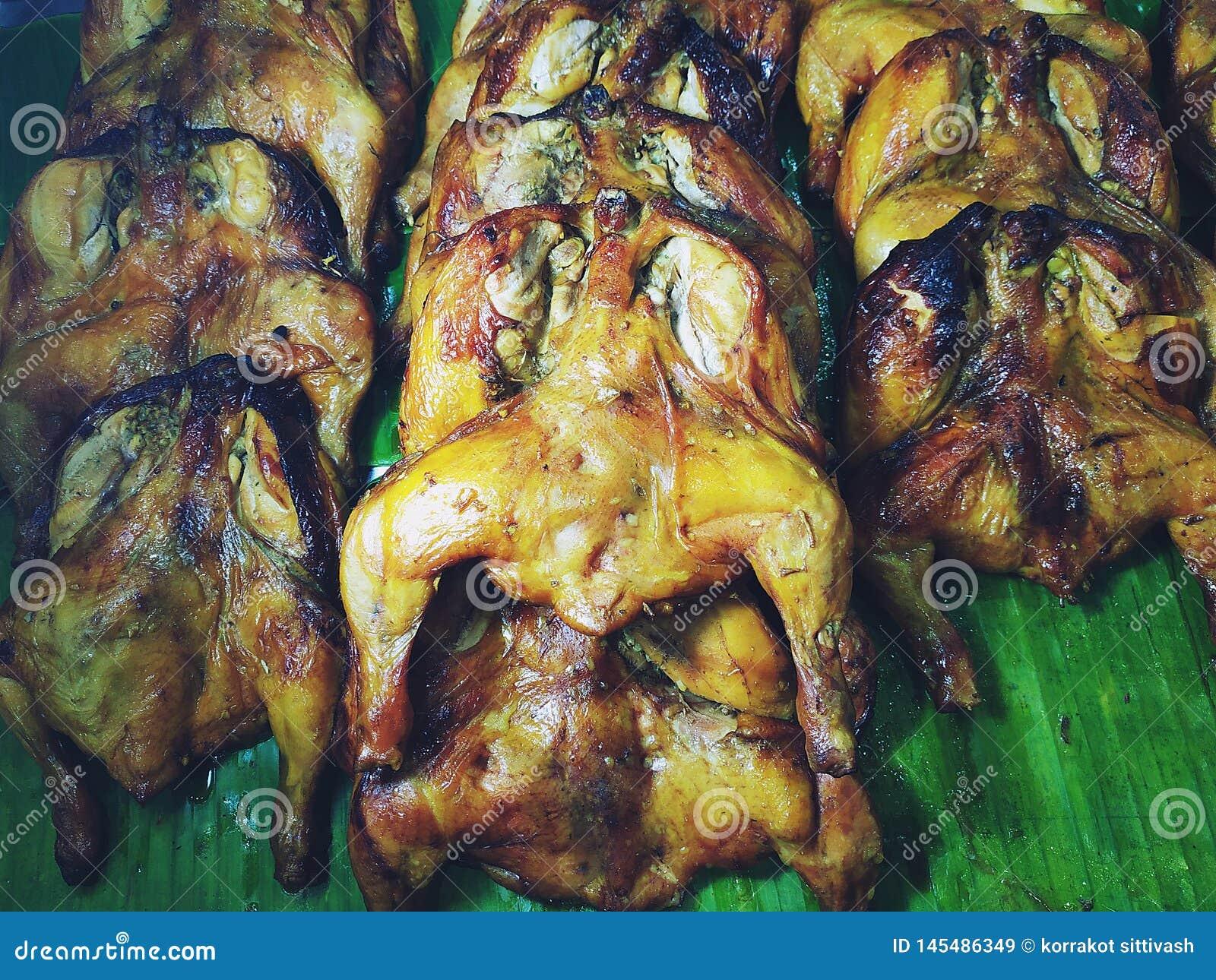 Frasig grilla höna som förläggas på banansidor