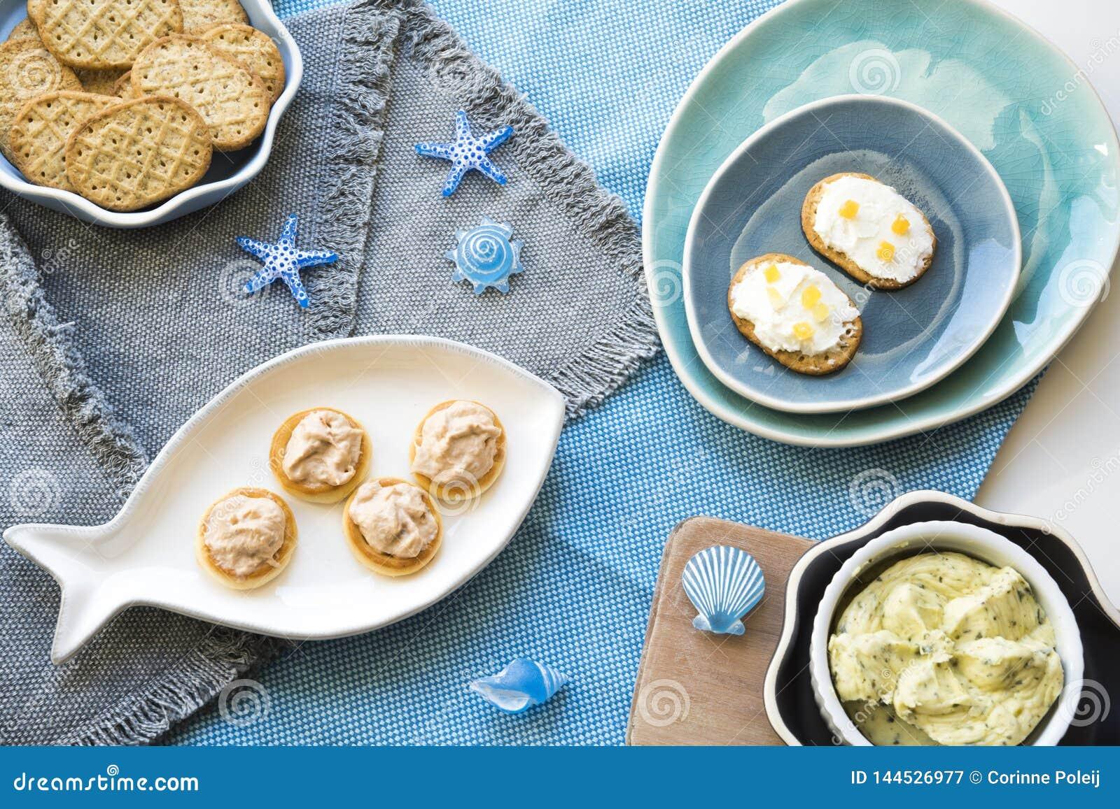 Frasiga rostade bröd på flera blåa plattor, med tonfisk- och laxsallad, gräddost och smör