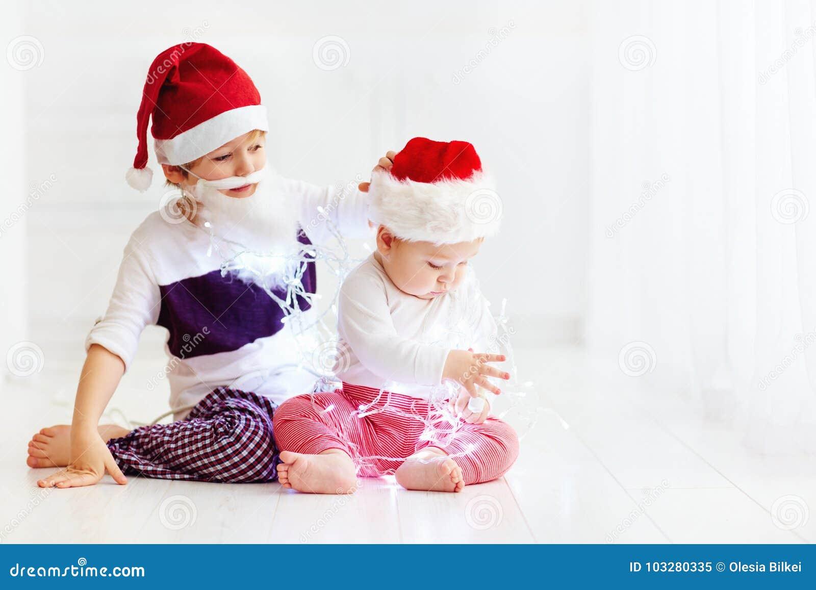 Fratelli germani svegli del fratello, bambini in cappelli del ` s di Santa e ghirlanda che gioca a casa