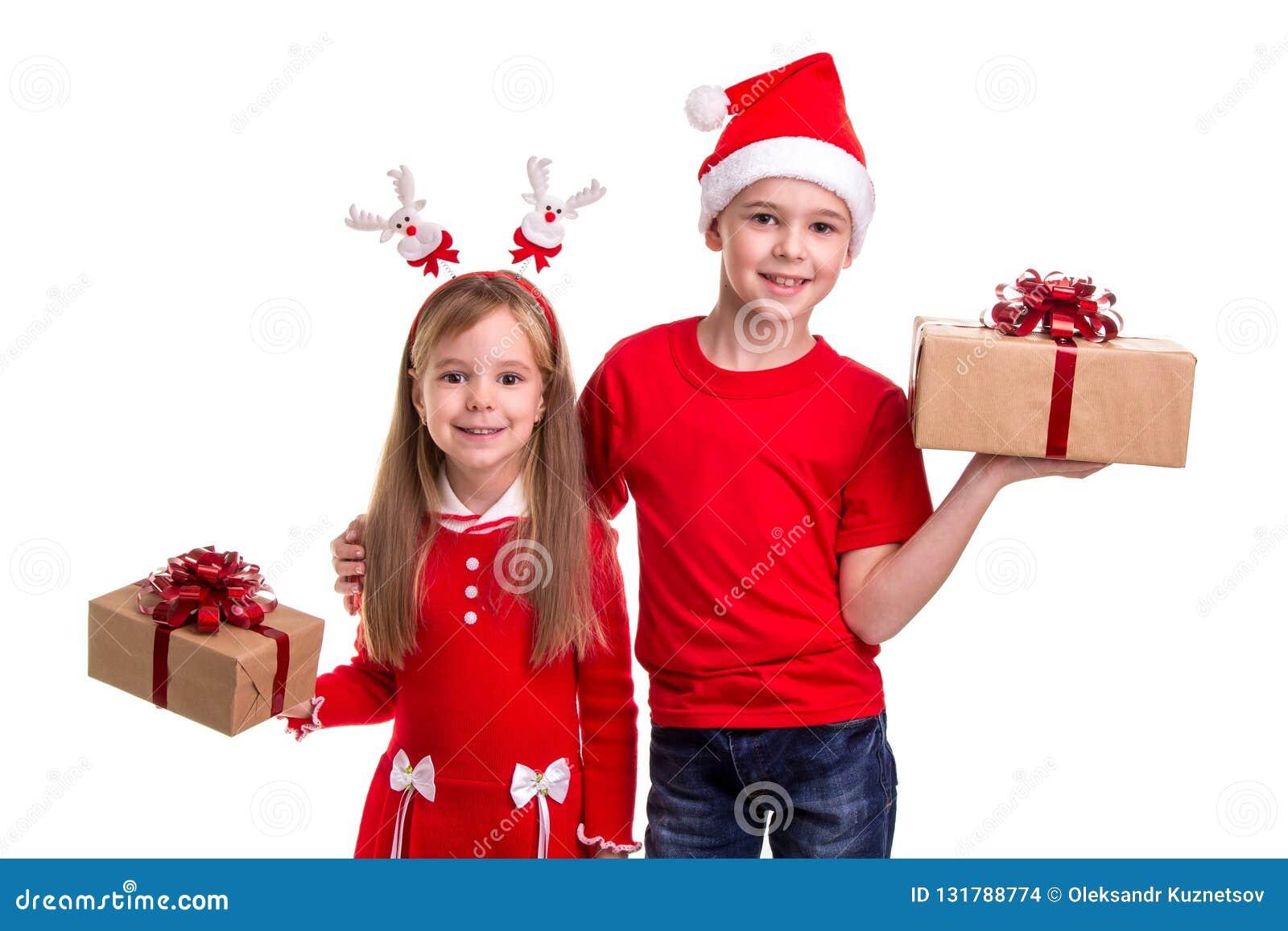 Fratello felice con il cappello di Santa sulla sua testa e su una sorella con i corni dei cervi, tenenti i contenitori di regalo