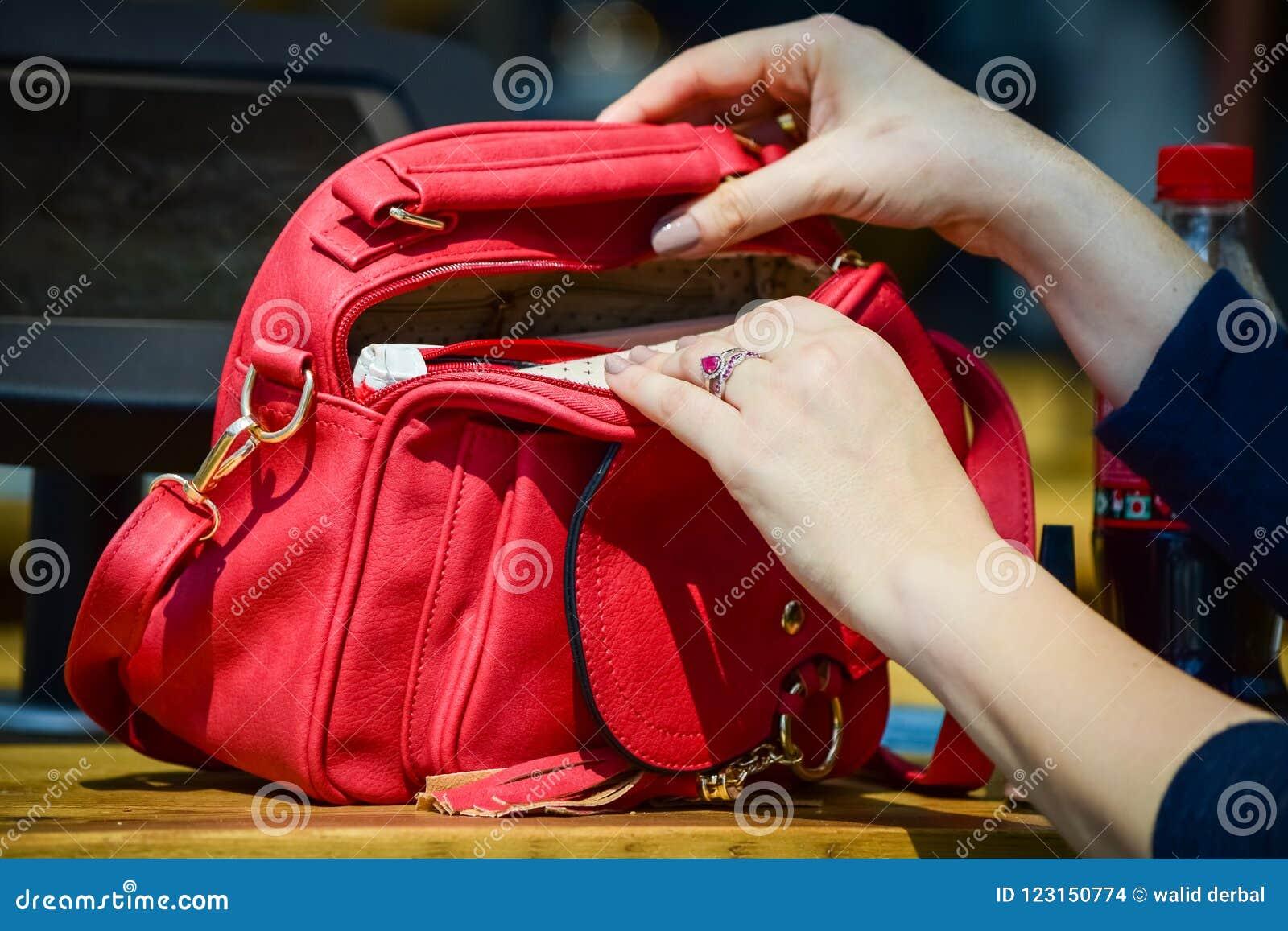 Frau übergibt öffnende rote Handtasche
