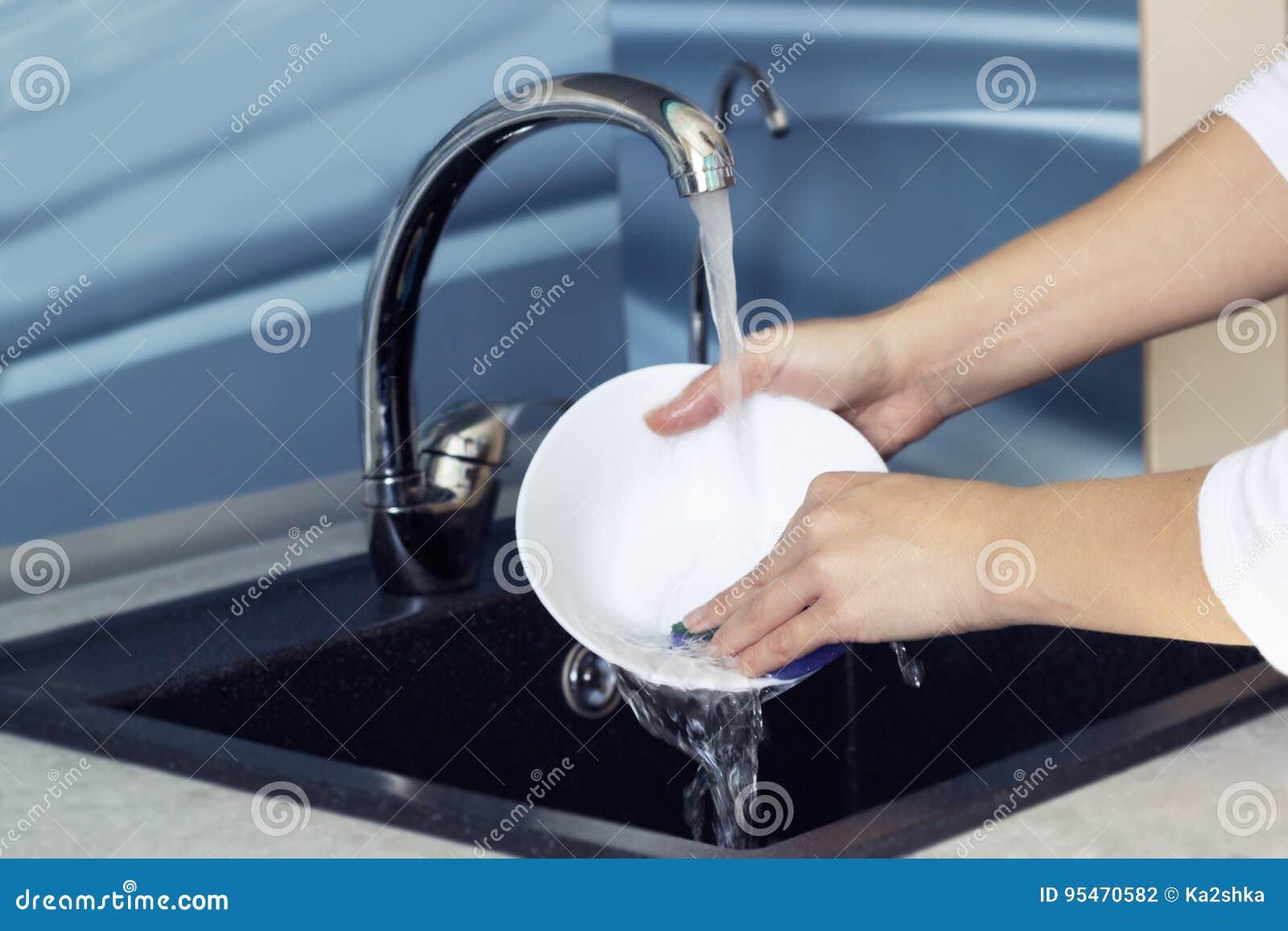Frau übergibt das Ausspülen von Tellern unter fließendem Wasser in der Wanne