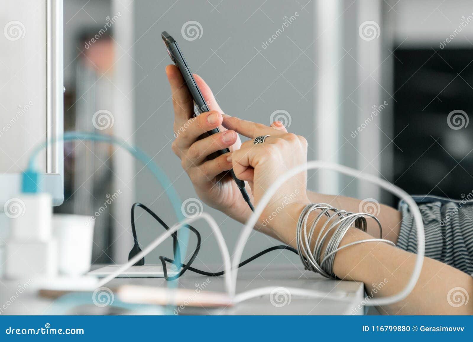 Frau übergibt holdingsmartphone bei der Aufladung es in einem Öffentlichkeitswinkel des leistungshebels