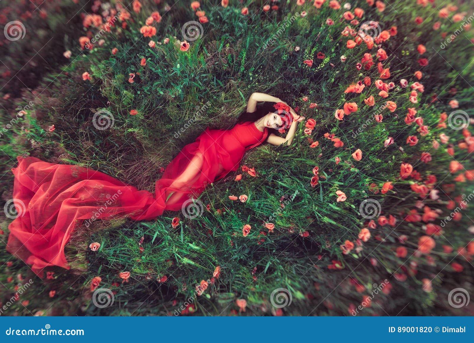 Frau auf dem Blumenmohnblumengebiet im Sommer