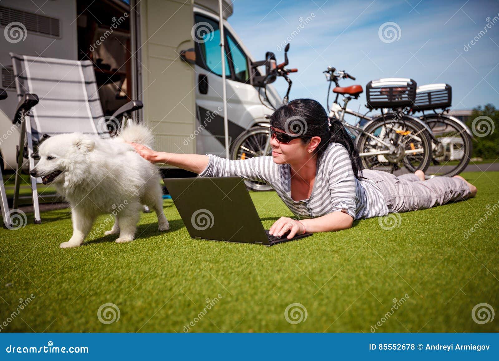 Frau auf dem Gras mit einem Hund, der einen Laptop betrachtet