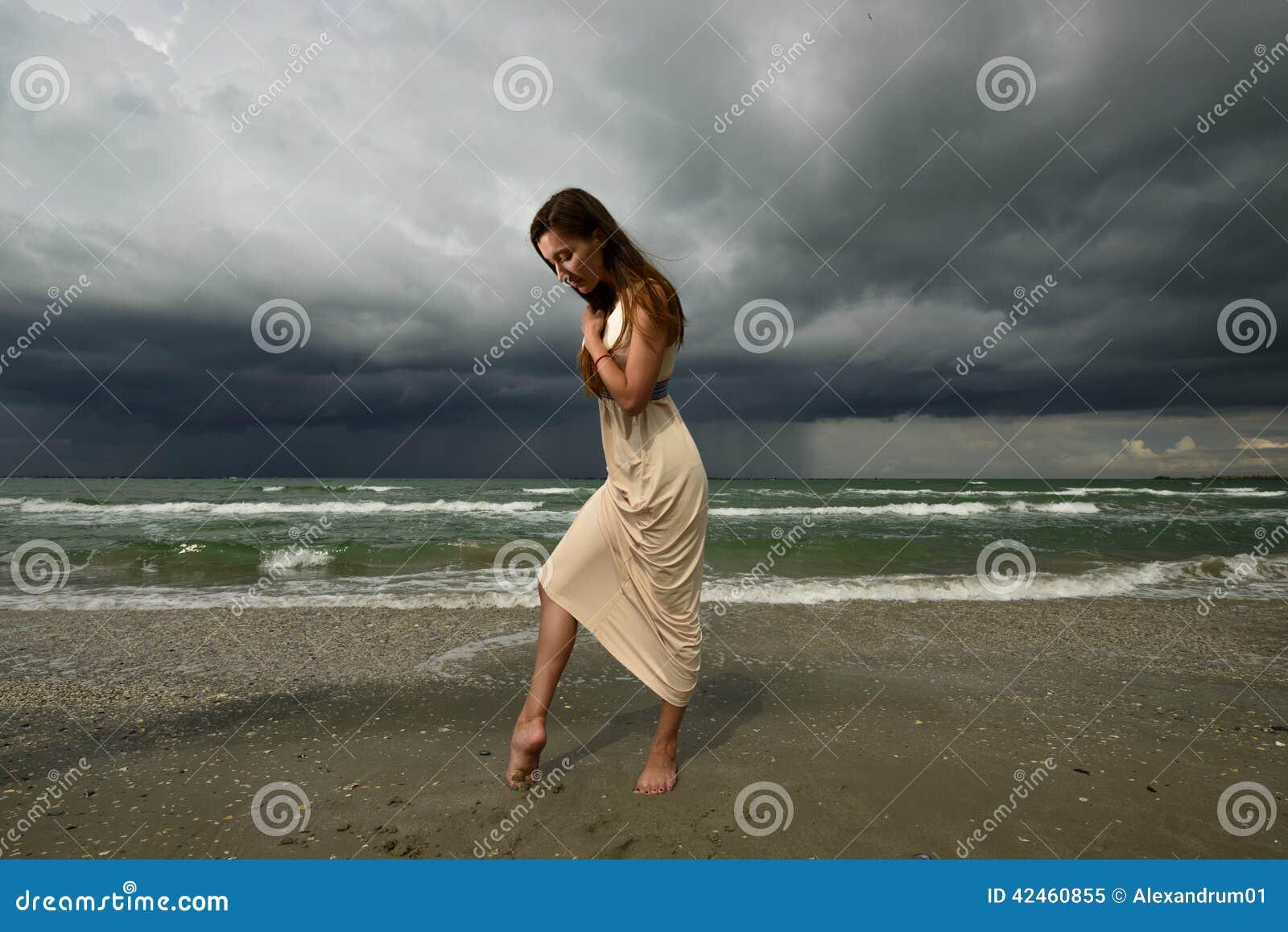 Frau auf einem Strand bei dem Sonnenuntergang