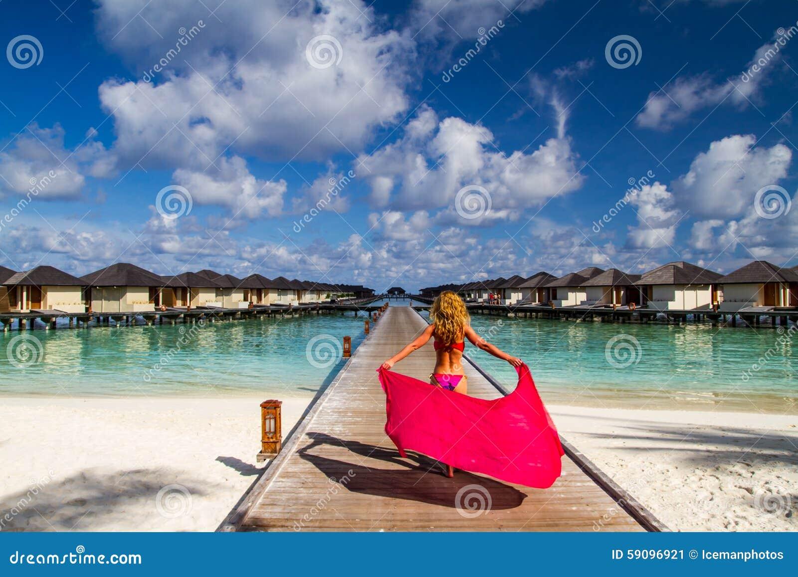 Frau auf einer Strandanlegestelle bei Malediven
