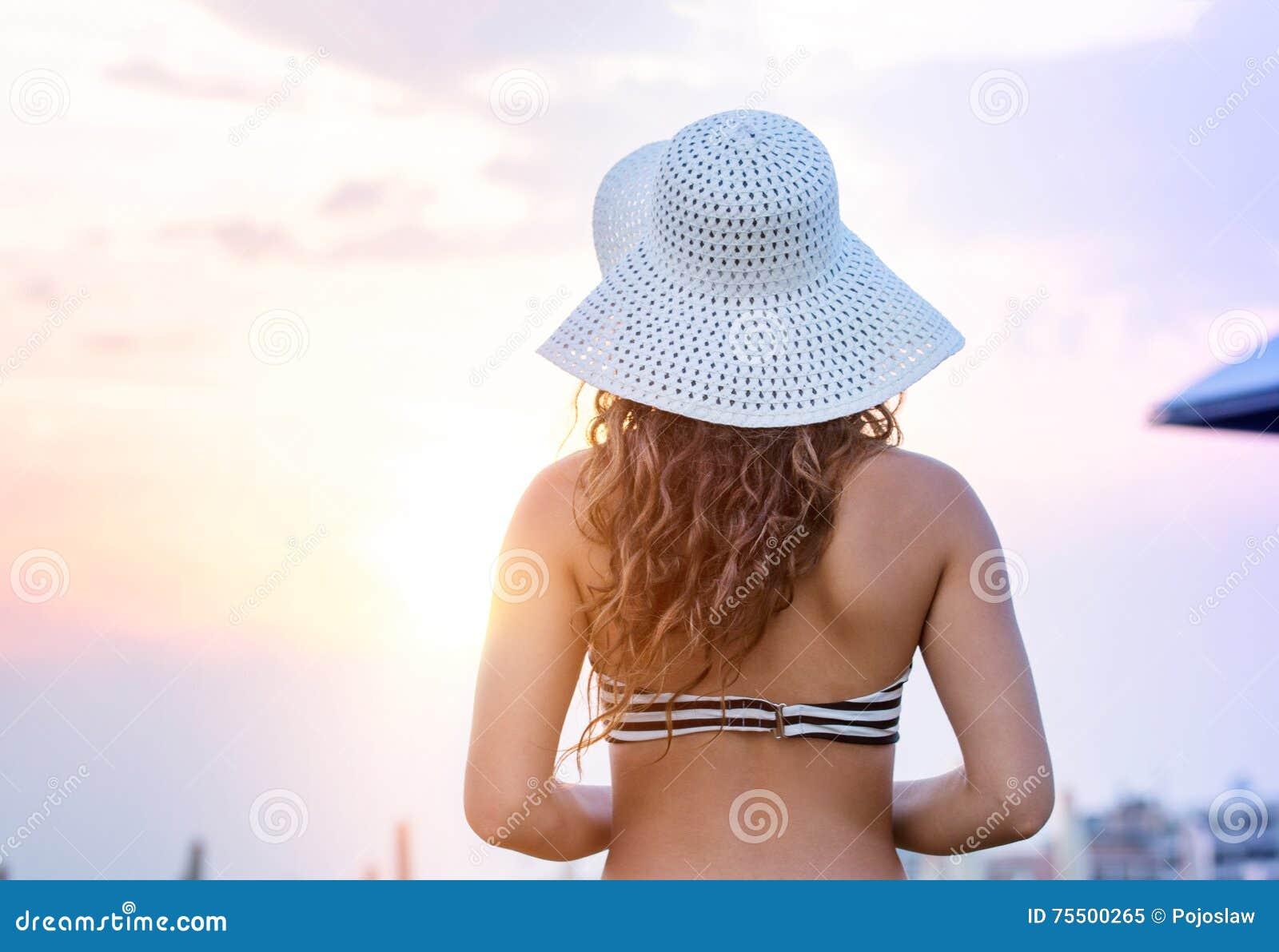 Frau auf tragendem Bikini des Strandes und Hut, hintere Ansicht