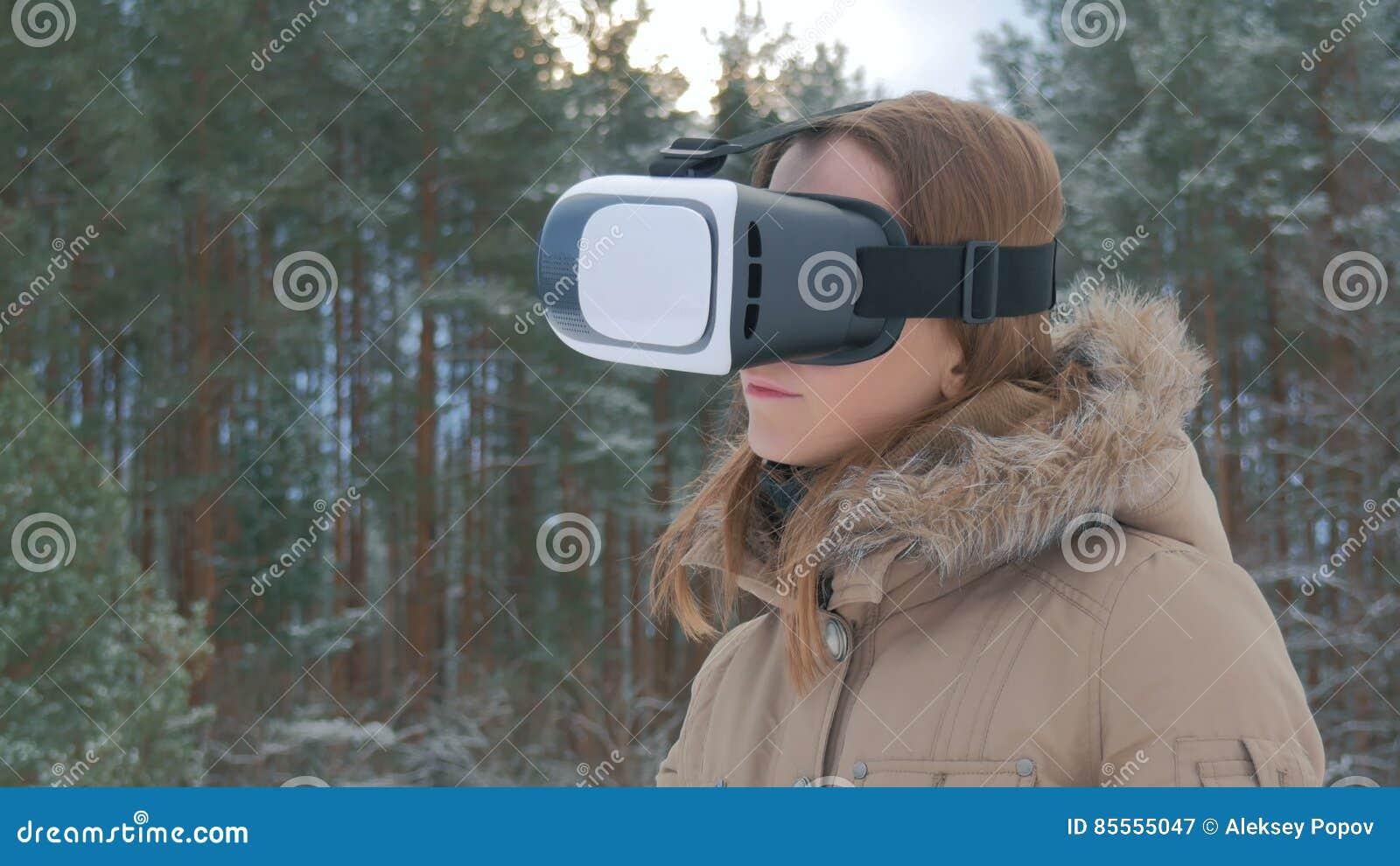 Frau benutzt Gläser einer virtuellen Realität im Winterwald