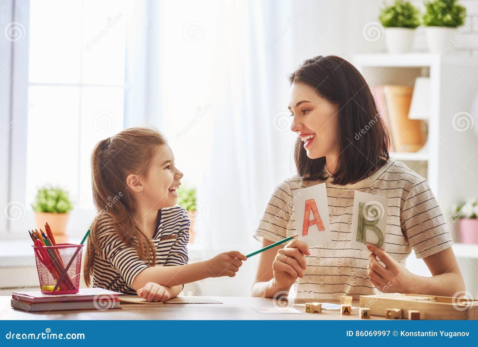 Frau bringt Kind das Alphabet bei