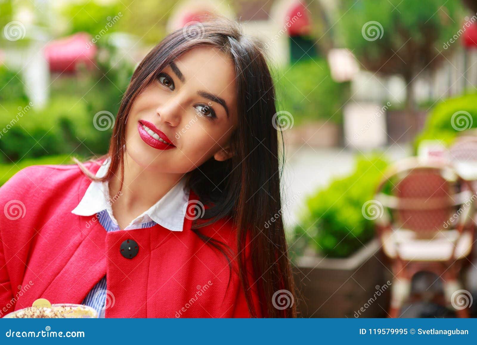 Frau in der glücklichen lächelnden schauenden Kamera der Cafékaffeestube