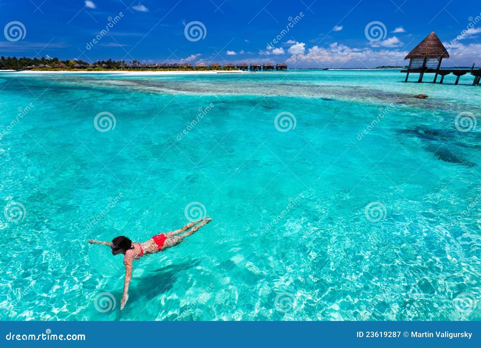 Frau in der roten Bikinischwimmen in einer korallenroten Lagune