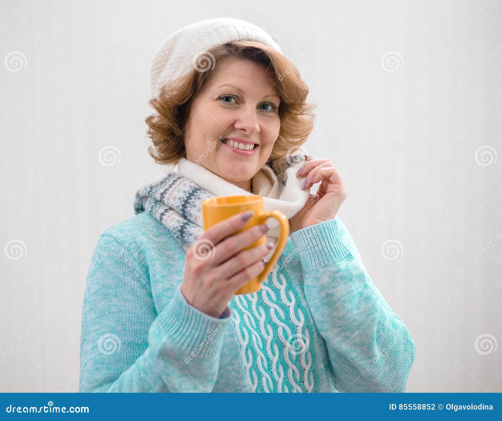 Frau in der Strickjacke, in Hut und in Schal, die gelbe Tasse Tee halten