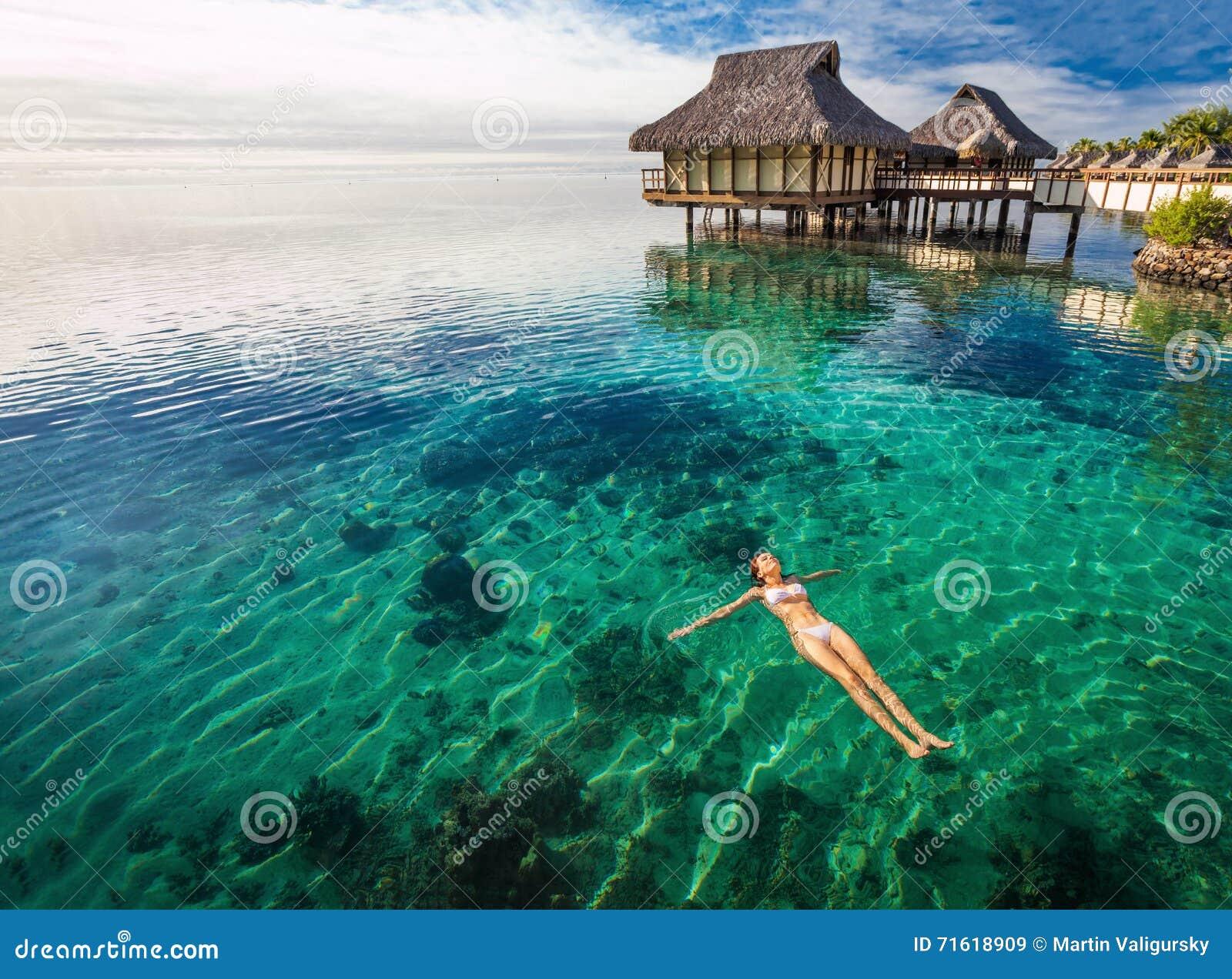 Frau in der weißen Bikinischwimmen in der korallenroten Lagune, Moorea, Tahiti