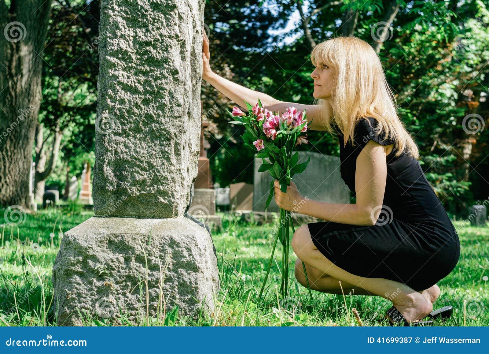Frau, die über Grab sich Sorgen macht