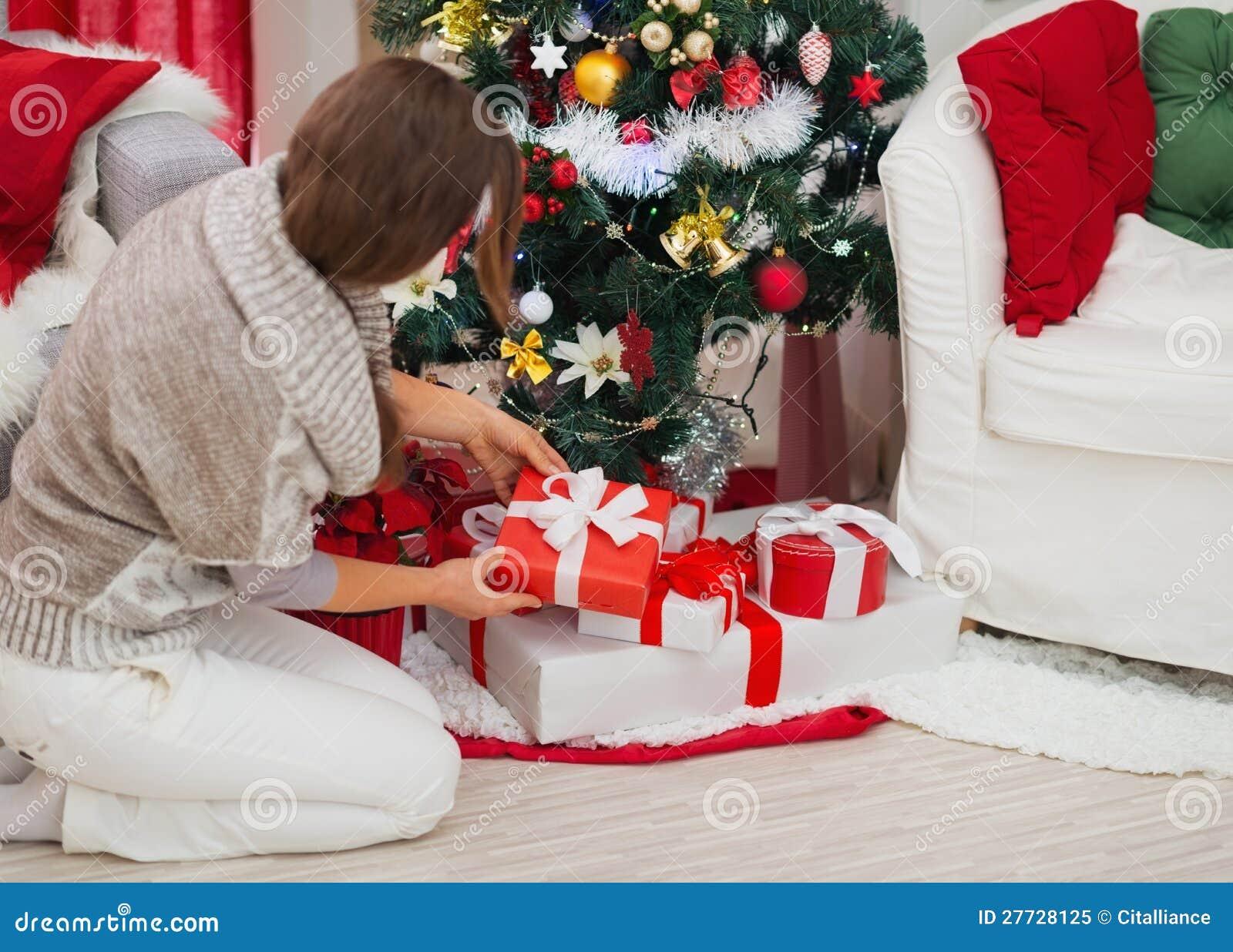 Frau, die anwesenden Kasten unter Weihnachtsbaum setzt