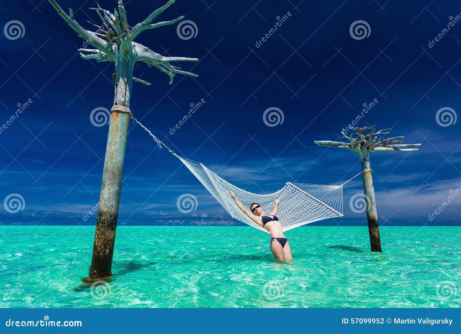 Frau, die auf Überwasserhängematte mitten in tropischem L sich entspannt