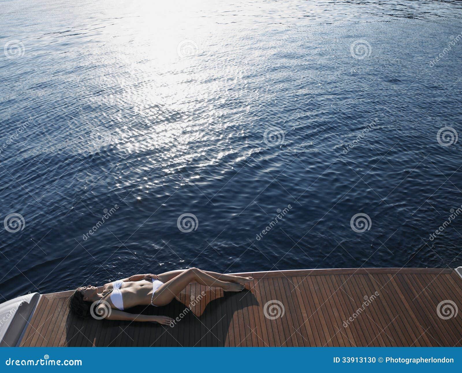 Fußboden Yacht ~ Frau die auf dem fußbodenbrett der yacht durch meer ein sonnenbad