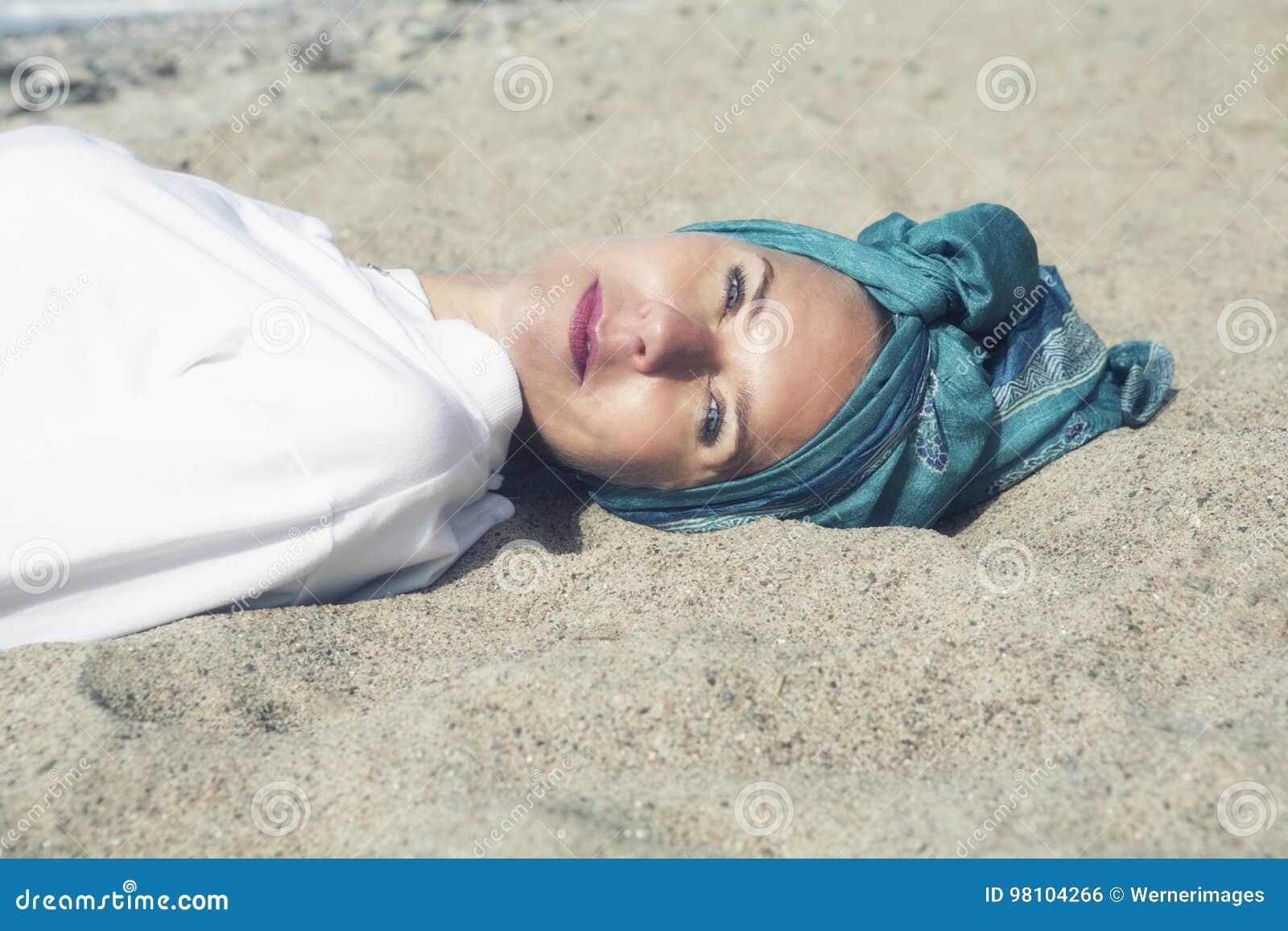 Frau, die auf dem Strand liegt und an der Kamera lächelt